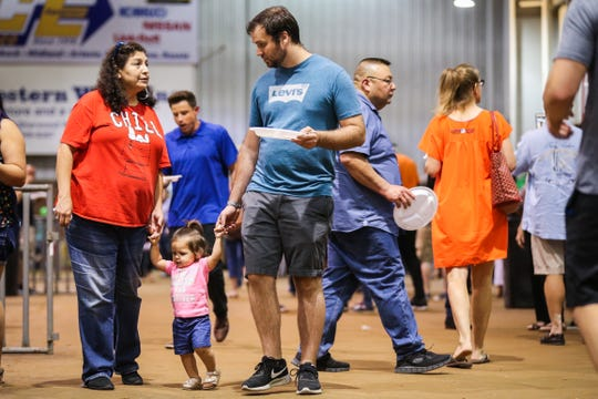 Ester Ybarra and Blake Corder help Carolyn Corder, 1, walk around during Taste of San Angelo Tuesday, Sept. 11, 2018, at 1st Community Federal Credit Union Spur Arena.