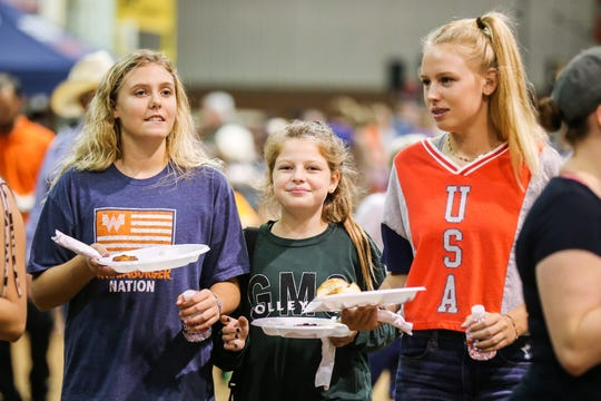 Zoe Olson, 14, Ann White, 12, and Adilee White, 14, walk around with plates of samples during Taste of San Angelo Tuesday, Sept. 11, 2018, at 1st Community Federal Credit Union Spur Arena.