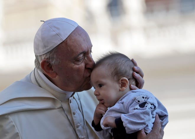 Pope Francis kisses a baby as he arrives in St. Peter's Square at the Vatican for his weekly general audience, Wednesday, Sept. 12, 2018.
