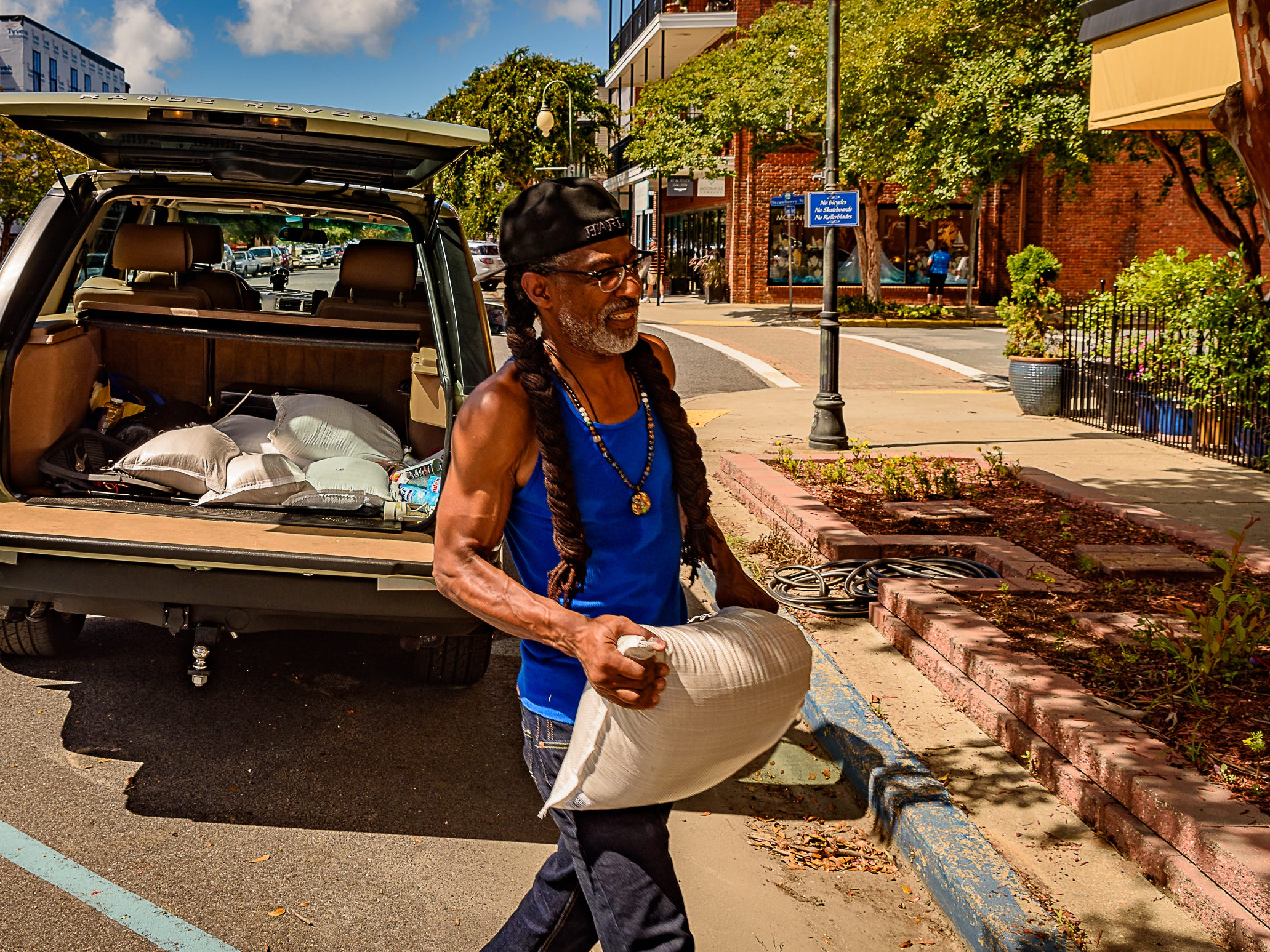 Local artist and Cape Charles resident Leland Sharp places sandbags in front of the Lemon Tree Gallery as Northampton County prepared for the approaching Hurricane Florence.