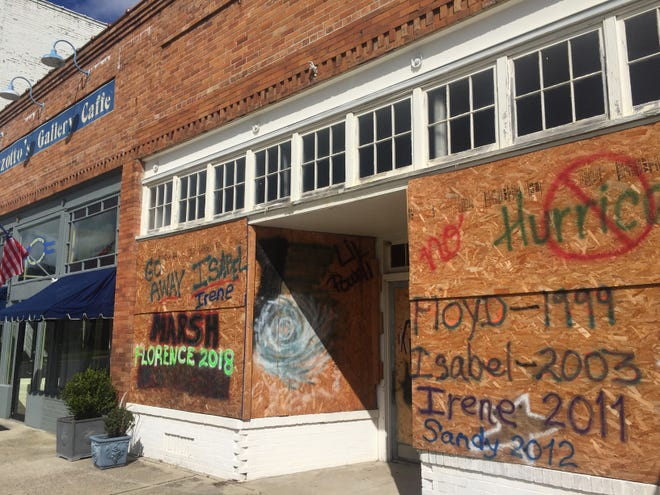 C. D. Marsh Jewelers in Onancock, Virginia is boarded up, but still open, on Wednesday, Sept. 12, 2018 in preparation for the arrival of Hurricane Florence. The owners have used the same boards to protect the store from hurricanes since Hurricane Floyd in 1999, as the paintings on the boards document.