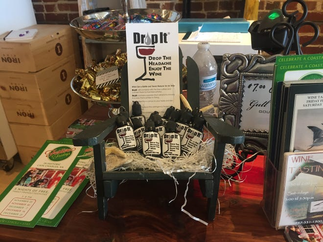 A display at Gull Hummock in Cape Charles, Virginia shows bottles of Drop It, a product invented and marketed by Jenny Corcoran, a Cape Charles resident. Corcoran created the product, which is meant to be added to a glass or a bottle of wine, to help people who suffer headaches after drinking even small amounts of wine due to a sensitivity to sulfites or tannins.