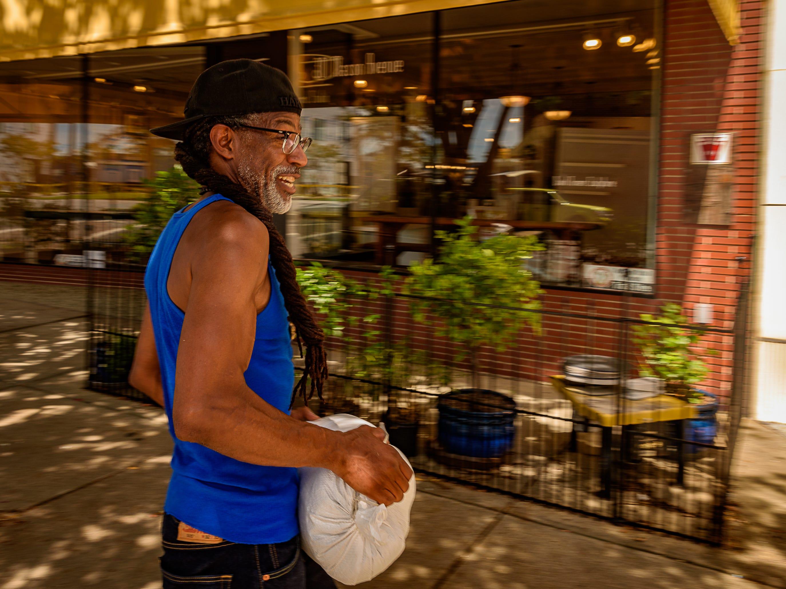 Cape Charles resident Leland Sharp stacks sandbags in front of Lemon Tree Gallery in preparation for Hurricane Florence.