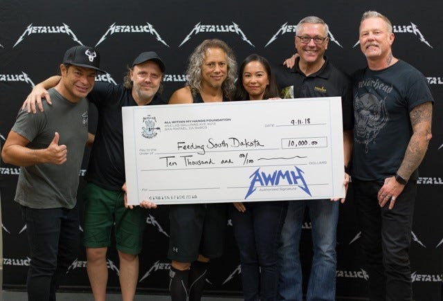 Feeding South Dakota CEO Matt Gassen and Development Director Christina Oey accept a $10,000 donation from Metallica on Tuesday night at the Denny Premier Center to help end hunger across the state.