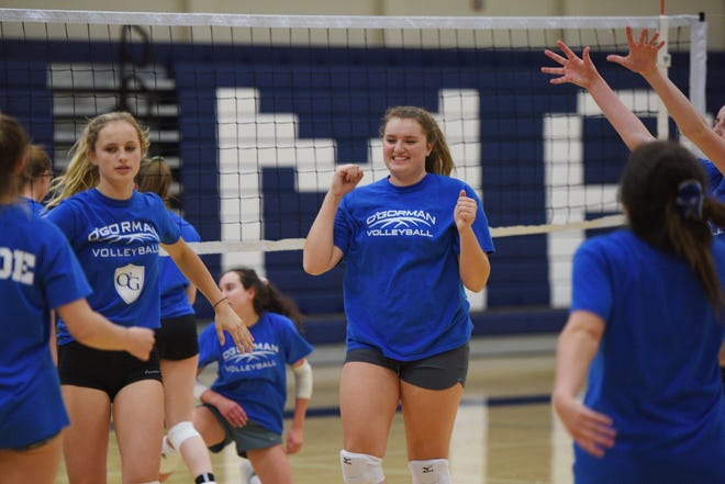 O'Gorman volleyball player Courtney Baruth, center, celebrates with her team during practice. The Knights rose to No. 1 (AA) in the latest Media Poll.