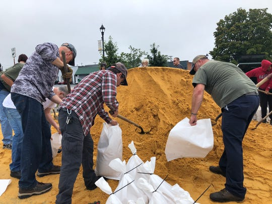 Residents and business owners making sandbags at the Arch Avenue parking lot in downtown Waynesboro.