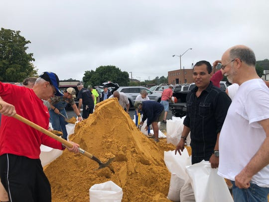 Residents and business owners making sandbags at the Arch Avenue parking lot in downtown Waynesboro. Pictured here is Joseph Laurenzo lending a hand.