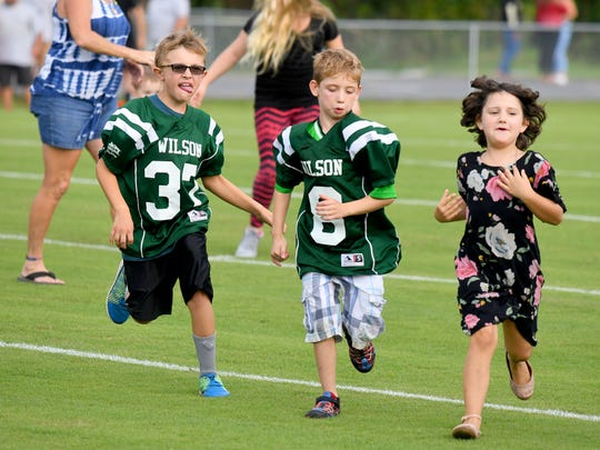 Pediatric cancer survivors run off the field after joining players for the coin toss just before kickoff of a game played in Fishersville on Wednesday, Sept. 12, 2018.