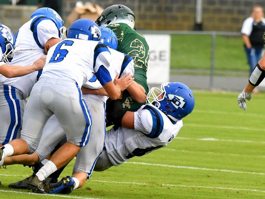 A mass of Fort Defiance players drag down and tackle Wilson Memorial ballcarrier Maurice Johnson during a game played in Fishersville on Wednesday, Sept. 12, 2018.