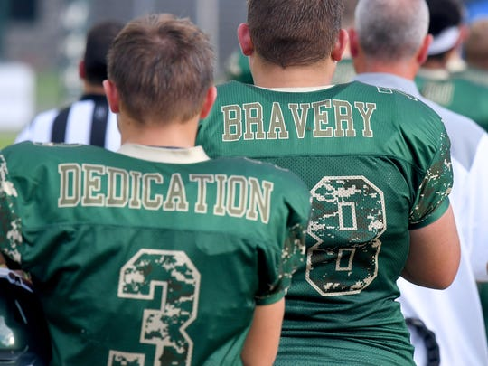 """On a night designated the """"First Responder's Bowl,"""" words like """"Dedication"""" and """"Bravery"""" adorn the back of Wilson Memorial uniforms during a game played in Fishersville on Wednesday, Sept. 12, 2018."""