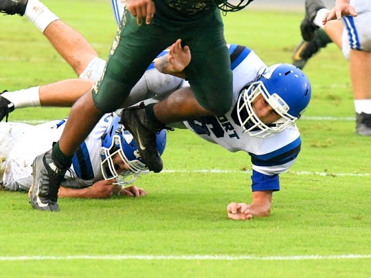 Fort Defiance's Colby Morris gets his arm around the leg of Wilson Memorial ball carrier Maurice Johnson to bring him down during a game played in Fishersville on Wednesday, Sept. 12, 2018.