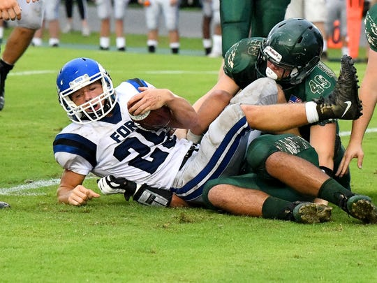 Fort Defiance's Trevor Bartley goes down as Wilson Memorial's Coby Spouse gets in on the tackle during a game played in Fishersville on Wednesday, Sept. 12, 2018.