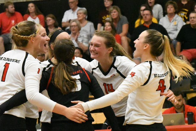 St. Cloud State volleyball players celebrate a victory over Minnesota-Duluth in an NSIC match Tuesday at Halenbeck Hall. The Huskies defeated the sixth-ranked Bulldogs 3-0. It was the first time St. Cloud State has defeated Minnesota-Duluth since 1995.