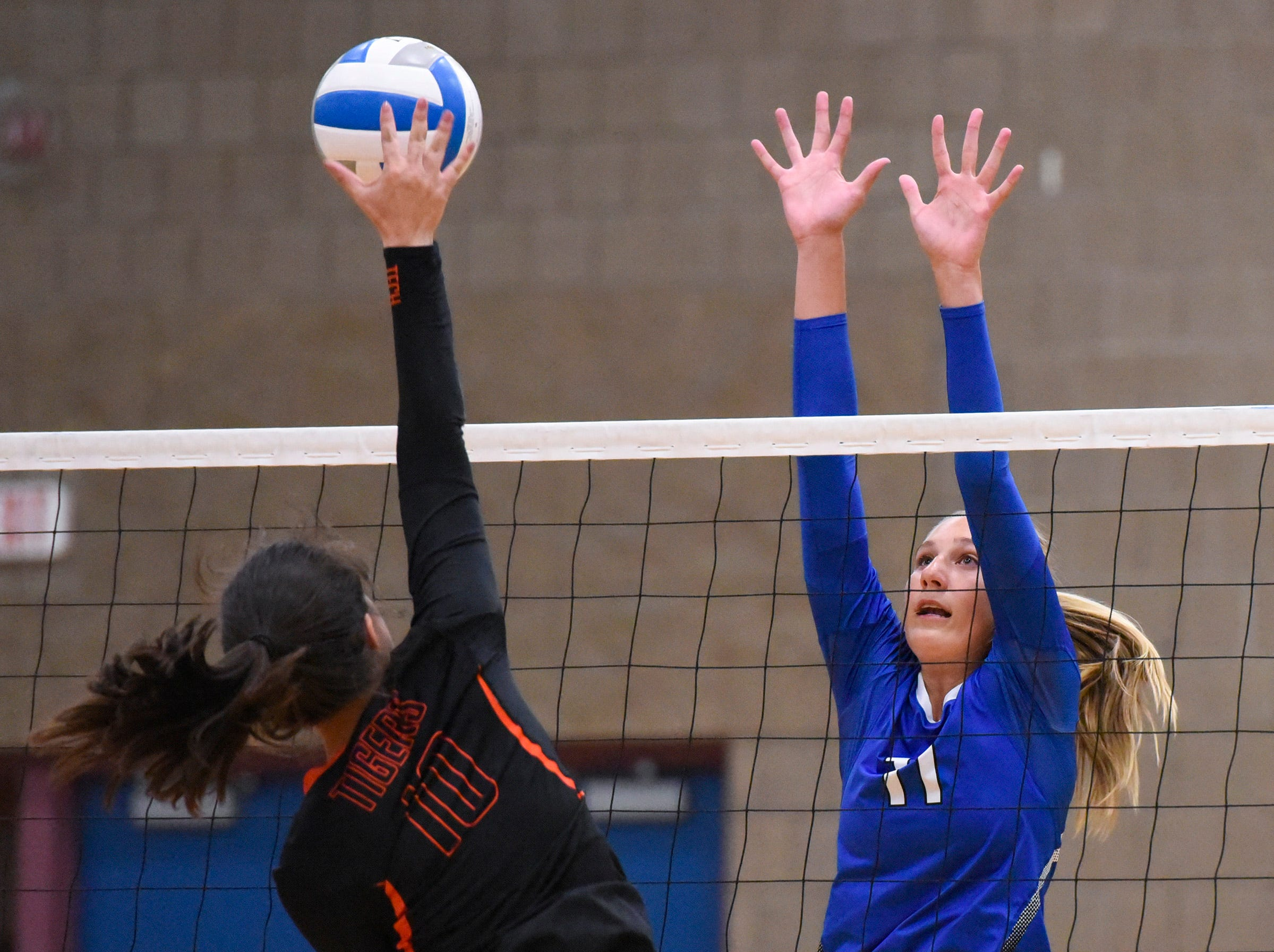 Tech's Ana Rivera tries to spike the ball past Sartell's Katelyn Hammer during the first game Tuesday, Sept. 11, in Sartell