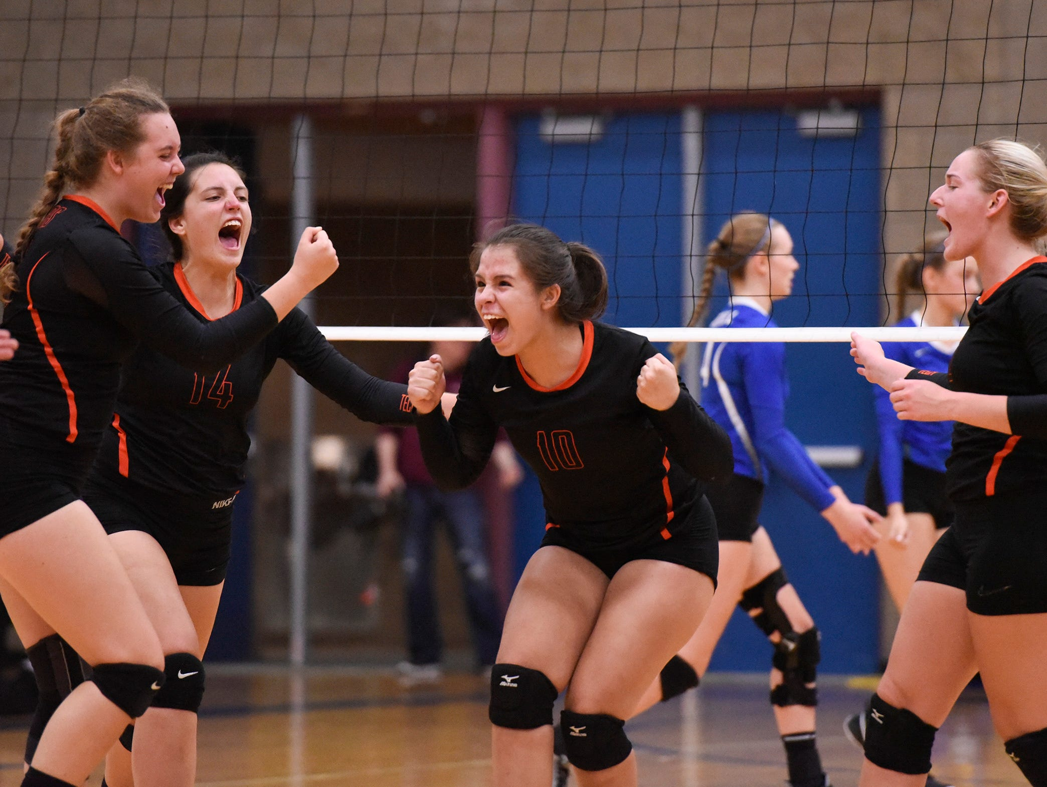 Tech players celebrate a point against Sartell during the first game Tuesday, Sept. 11, in Sartell