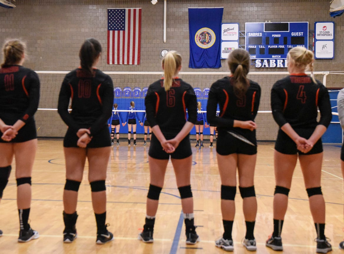 Sartell and Tech players stand for the National Anthem before the start of the game.