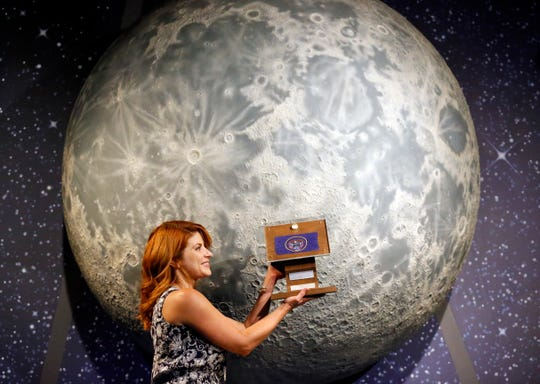 Lindsie Smith, from the Clark Planetarium, holds moon rocks encased in acrylic and mounted on a wooden plaque at the Clark Planetarium, in Salt Lake City. A former NASA investigator who has spent more than a decade tracking missing moon rocks is closing in on his goal of finding all 50 lunar samples gifted to U.S. states after Neil Armstrong's first steps on the moon. In recent weeks, two more of the moon rocks that dropped off the radar after the 1969 Apollo 11 mission have been located in Louisiana and Utah.