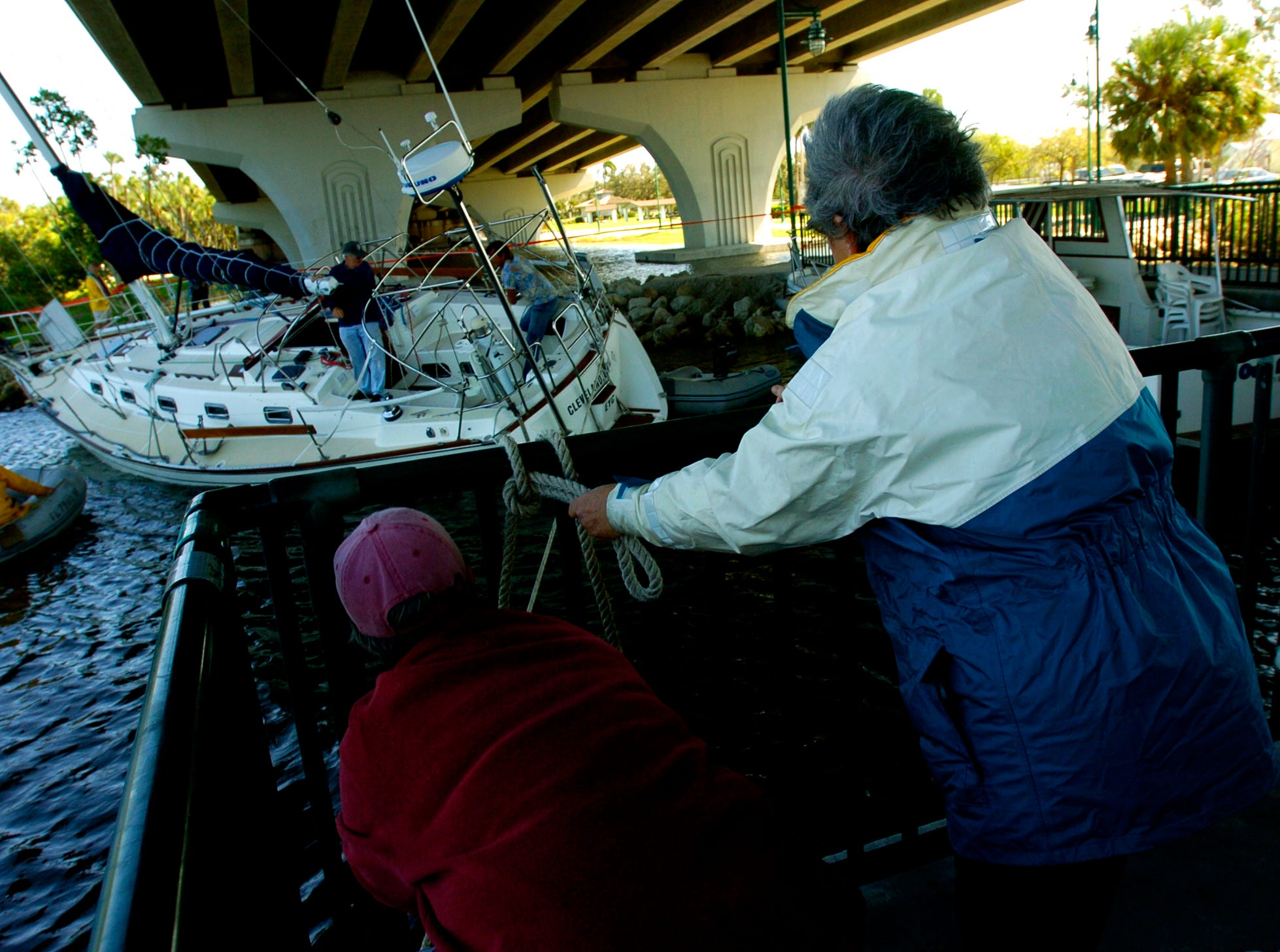 October 25, 2005 - Boat owner Chris Pierce (right) and friend Monique Griffin untie one of the lines as their husbands and friends help them free the Pierce's sailboat which broke free and crashed into a piling of Vero Beach's Barber Bridge during Hurricane Wilma. Chris Pierce and her husband Captain Richard Pierce decided to remove the vessel themselves after they received high price quotes to have someone else do it for them.