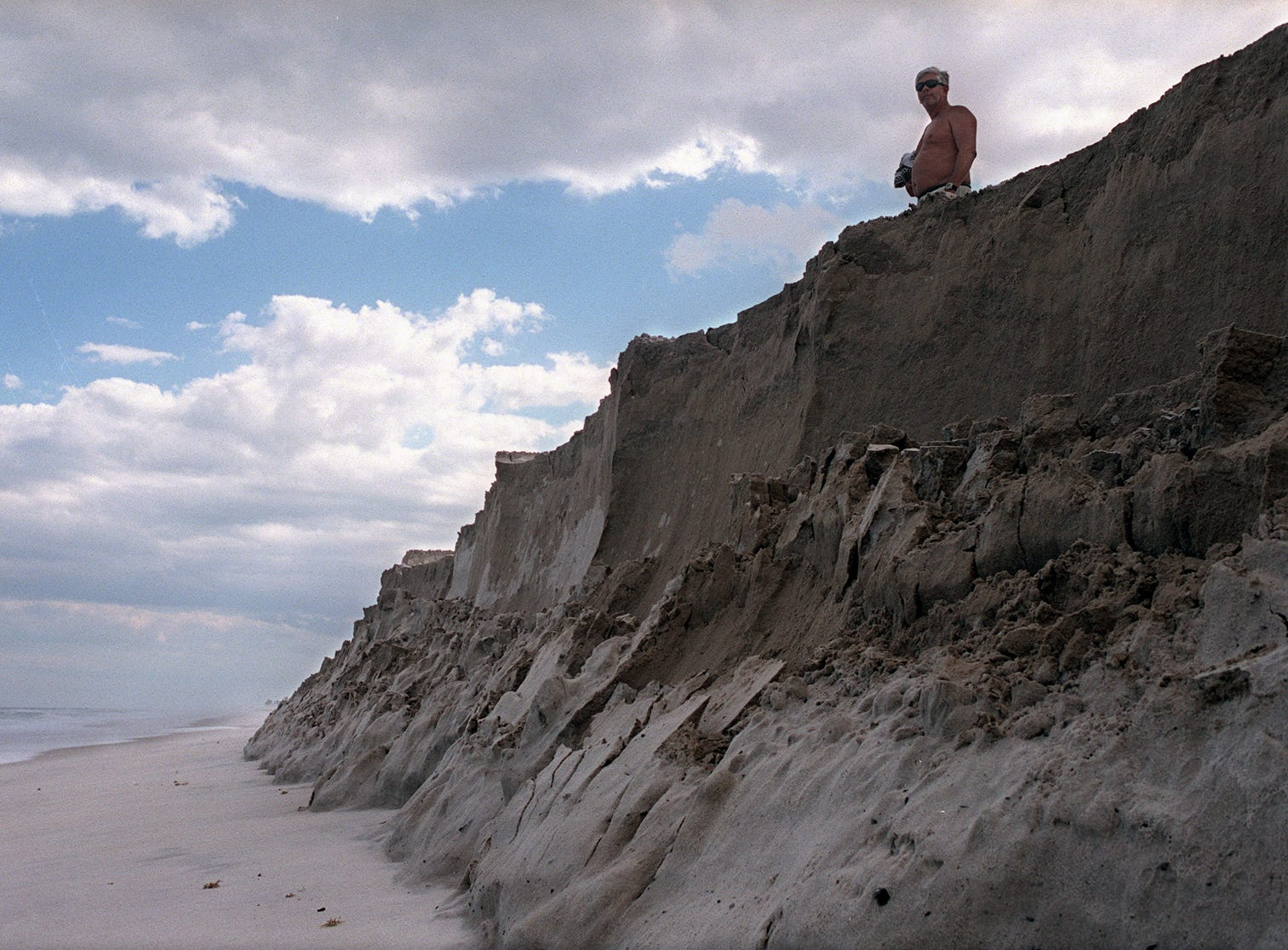 February 18, 2002 - Standing atop a newly dumped sand plateau, beachgoer Bill Leonard surveys a deserted stretch of beach just south of the Sebastian Inlet. Sand is being trucked to the area to try to prevent beach erosion.