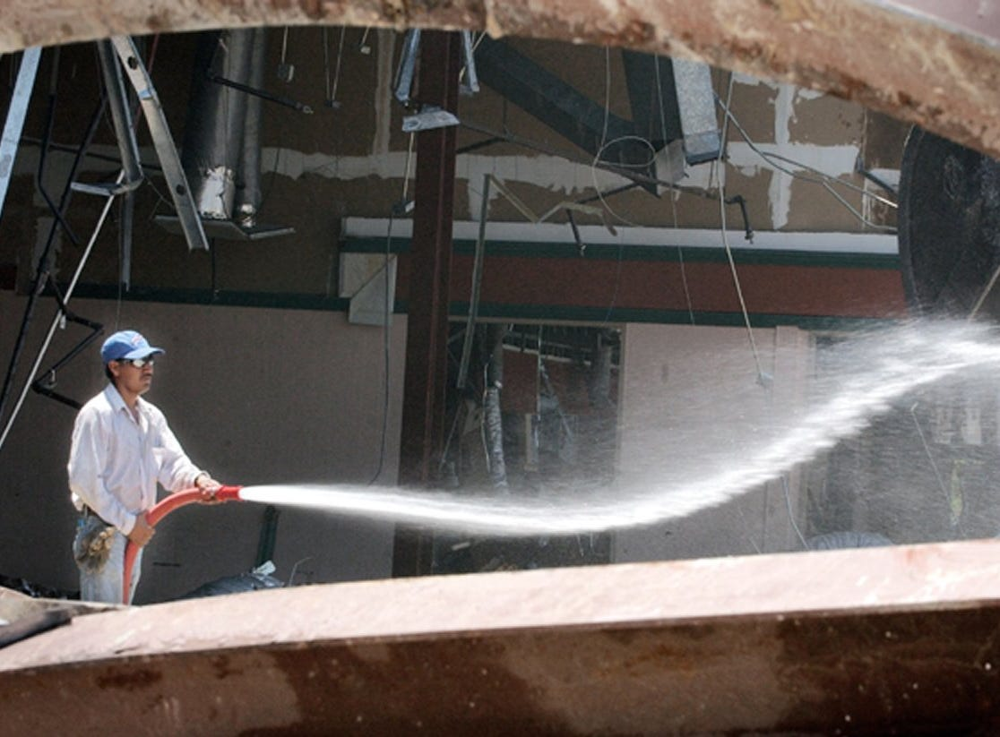 May 2, 2002 - Fermin Arriaga, of Cushing Demolition, sprays down the old Vero Mall to try to keep dust from flying while the building was being torn down. Paul Hanna Management Inc., of West Palm Beach, planned to reduce the 173,686-square-foot closed indoor mall into a 150,188-square-foot strip shopping center which will include a Publix Supermarket. The project was expected to be completed sometime in 2003.