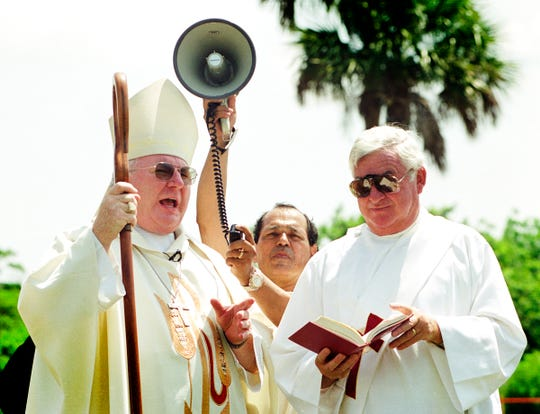 June 17, 2001 - Bishop Anthony O'Connell (left) addresses the crowd at Our Lady of Guadalupe Catholic Mission in Fellsmere, as parishioner Duber Bedoya holds the bullhorn amplifier for him and Deacon Hank Toussaint holds the Bible during groundbreaking ceremonies for a new multipurpose building on the church grounds. The mission was expanding for a new 7,500-square toot building to house its food distribution program and educational classrooms.
