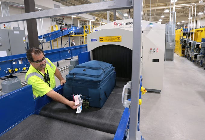 Oscar Apodaca feeds bags into a 3D scanner in the El Paso International Airport's new checked baggage inspection area. The airport recently completed their $27.5 million system.
