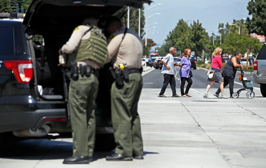 People are evacuated as Los Angeles County sheriff's deputies prepare to stand guard Tuesday at Kaiser Permanente Downey Medical Center after reports of someone with a weapon.