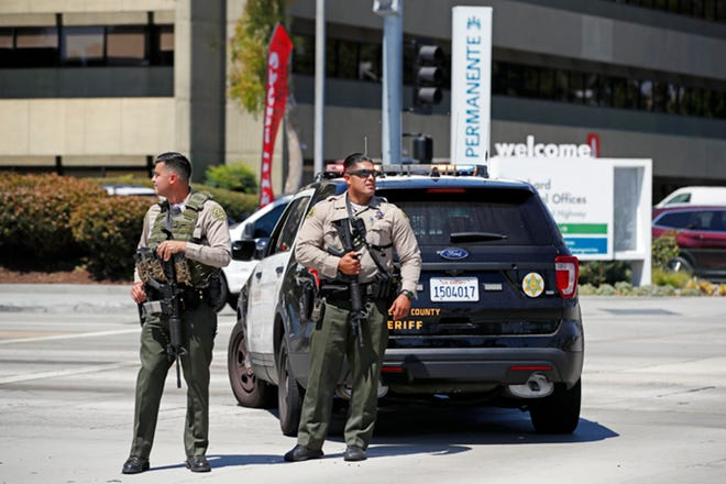 Los Angeles County sheriff's deputies stand outside after staff and patients were evacuated from Kaiser Permanente Downey Medical Center after reports of someone with a weapon at the facility.