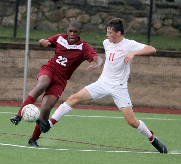 Tyler Shaw of Ossining battles Ketcham's Garrett Poorman during a varsity soccer game at Ossining High School Sept. 12, 2018. Ossining defeated Ketcham 5-2.