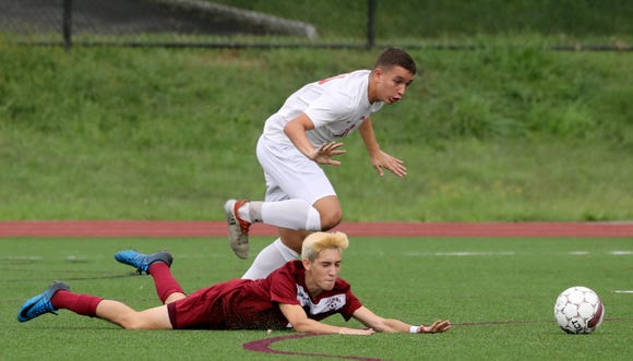 Mateo Marra of Ossining falls to the turf while he battles Ketcham's Kevin Vorfi during a varsity soccer game at Ossining High School Sept. 12, 2018. Ossining defeated Ketcham 5-2.