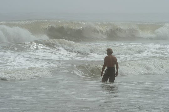 A beachgoer walks out into the waves at Rehoboth Beach.