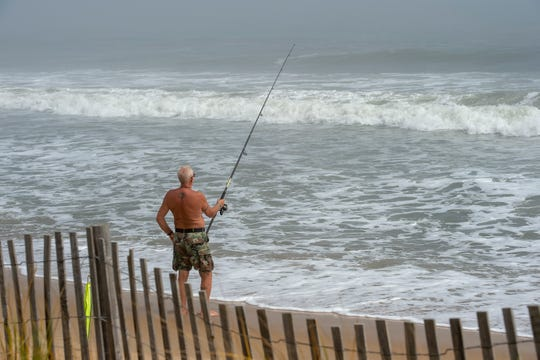 A beachgoer fishing at the north end of Rehoboth Beach.