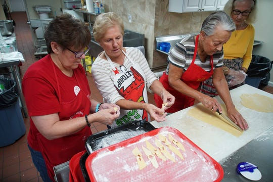 St. Hedwig's Church volunteers, from left, Kathy Dunworth, Nancy Lagowski and Sally Fillion tie dough into ribbon shapes while making traditional chrusciki cookies for the upcoming Polish Festival.