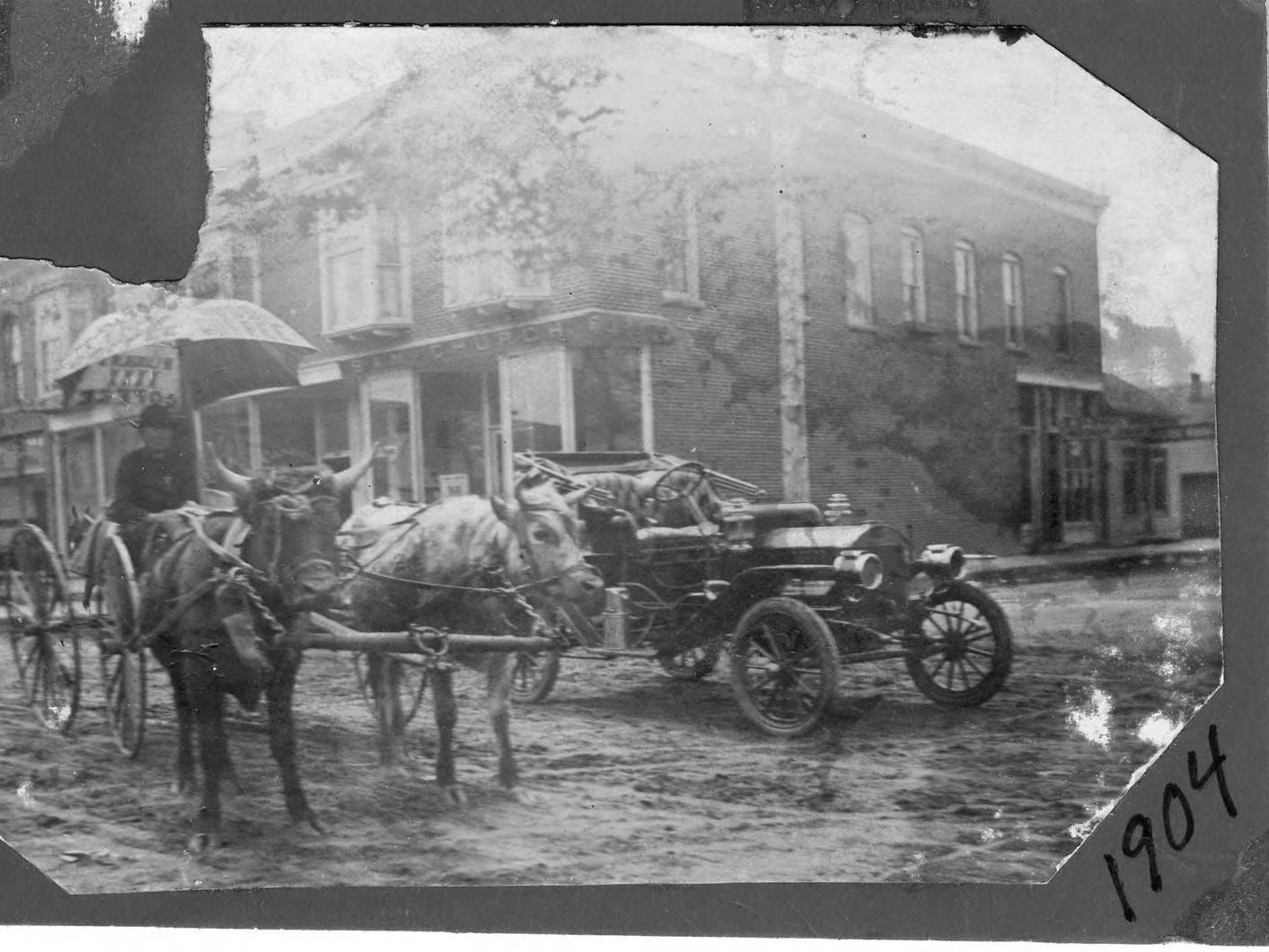 An automobile and a cattle team and carraige in front of Church's Drug Store in 1904