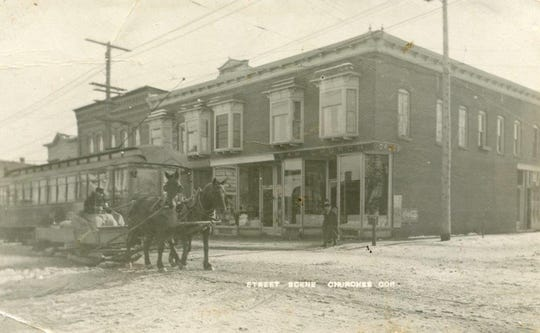 This photo of Church's Drug Store building also features a street car and a horse team pulling a sleigh.