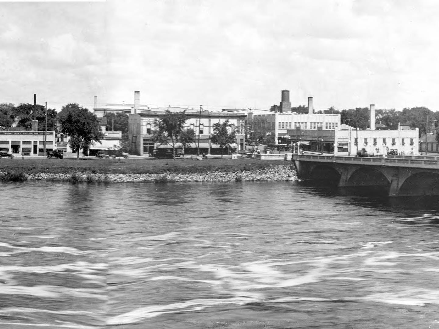 "A photo of the ""new bridge"" shows the River Block, Nash Hardware Company, the Wisconsin Rapids Daily Tribune, Normington's Laundry and the Wisconsin Valley Dairy Company."