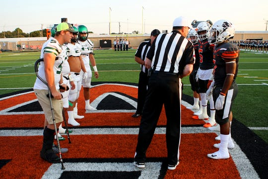 Iowa Park and Burkburnett players meet before the coin toss of last year's game.