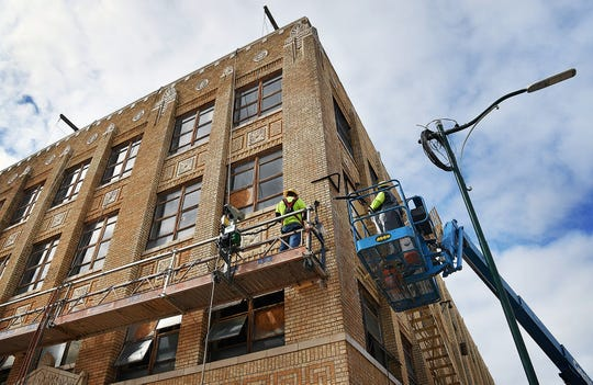 Workers with Mid-Contenental Restoration clean and repoint the brickwork of the former Maskat Temple building on Lamar. The building is being renovated for affordable downtown housing.