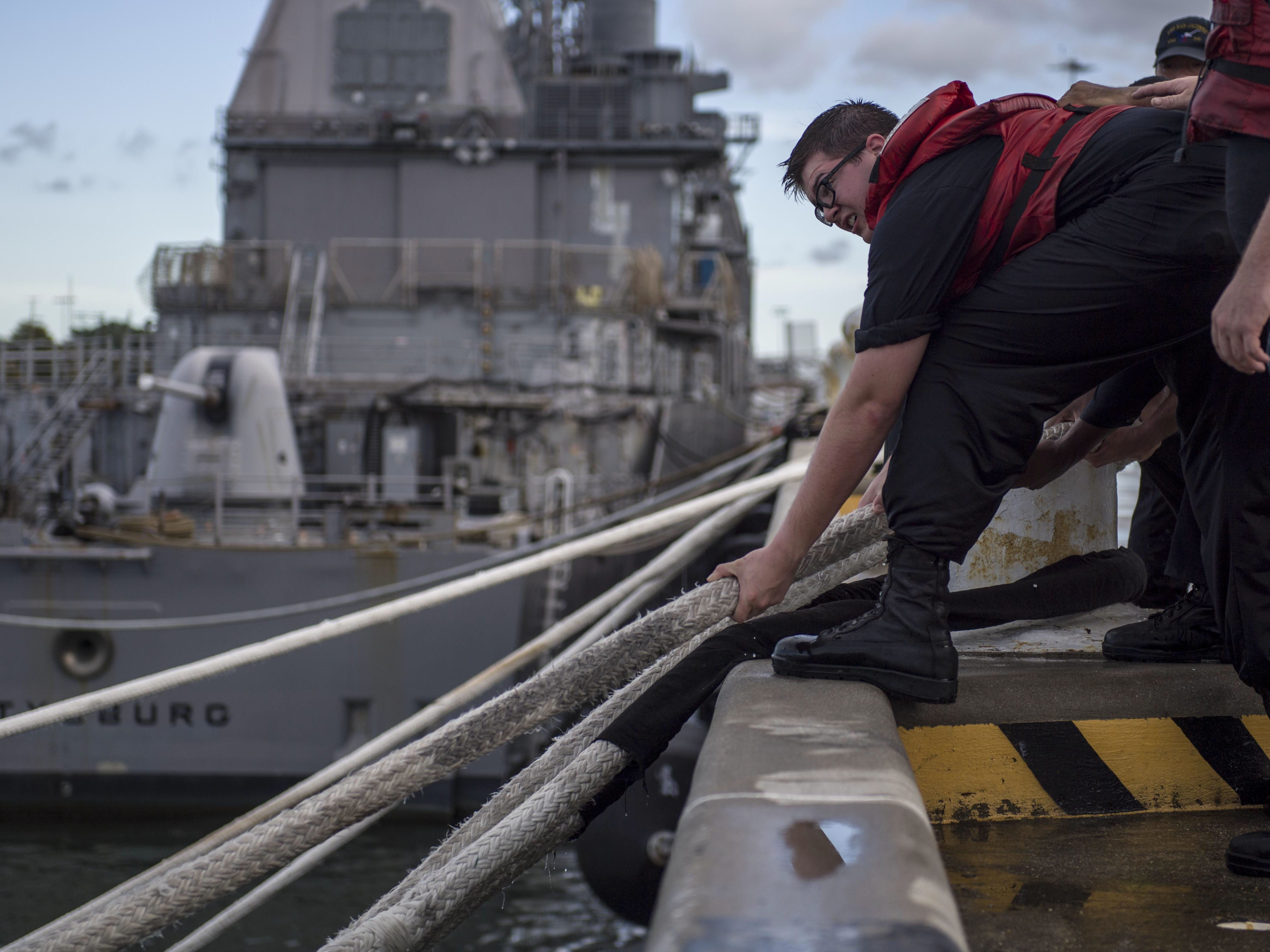 This US Navy photo released September 12, 2018 shows a Sailor as he heaves line during a heavy weather mooring evolution in preparation for Hurricane Florence on September 11, 2018 in Norfolk, Virginia. - Some ships will not get underway due to maintenance and are taking extra precautions to avoid potential damage. Commanding officers have a number of options when staying in port. Some of these options include adding additional mooring and storm lines, dropping the anchor, and disconnecting shore power cables.