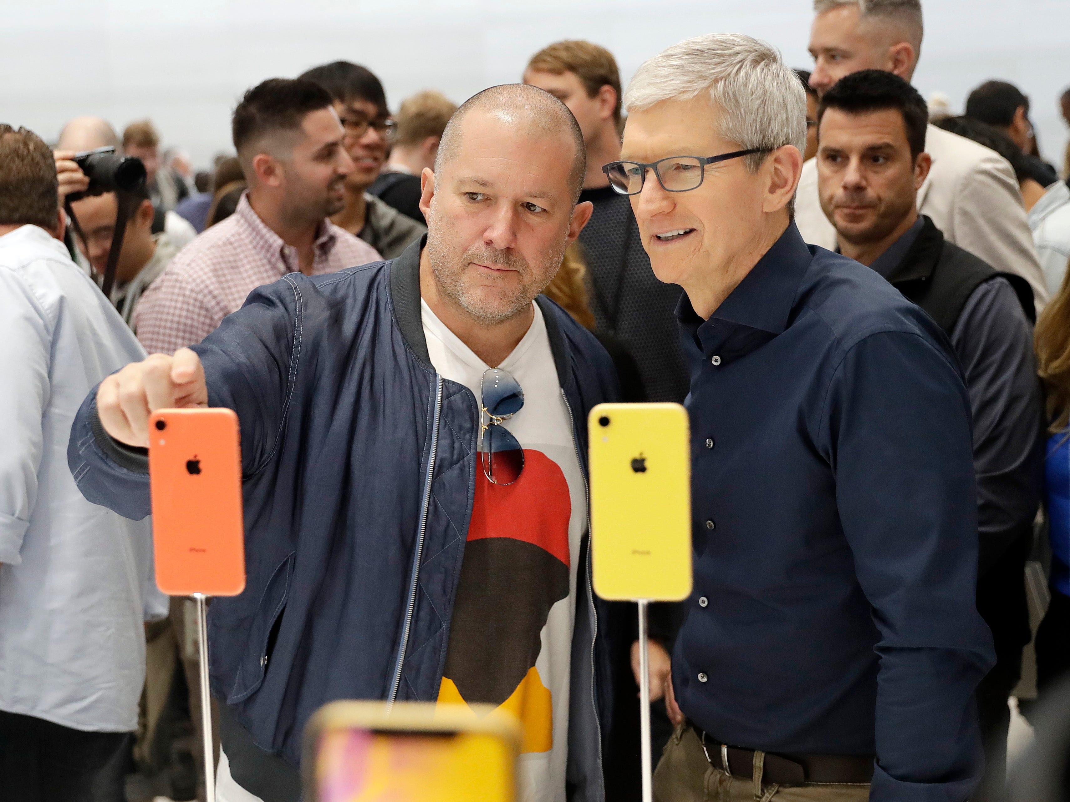 Jonathan Ive, Apple's chief design officer, left, looks at some new iPhone models with CEO Tim Cook during an event to announce new products Wednesday, Sept. 12, 2018, in Cupertino, Calif.