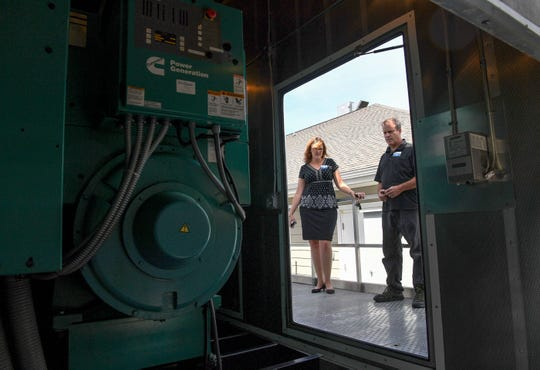 Bonnie Skobel, left, an administrator at the Trinity Grove Nursing Home in Wilmington, N.C., looks at a 750 Kilowatt generator with Pete Nero, the director of facilities, on Sept. 12, 2018.
