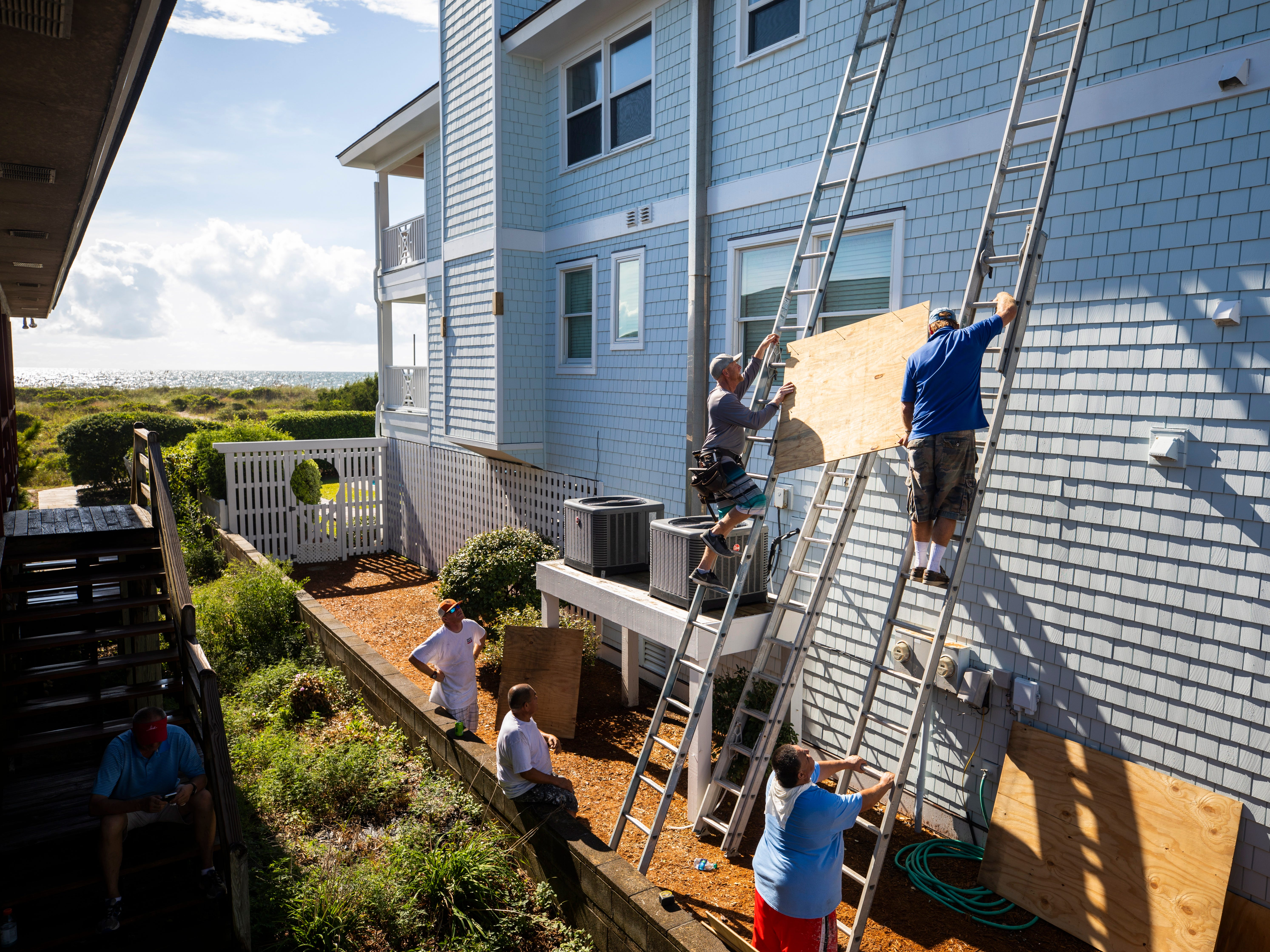 epa07014998 Bobby Vorn (top left) and Butch Beaudry (top right) prepare to attach wooden planks over the windows of an oceanfront home, less than two days before Hurricane Florence is expected to strike Wrightsville Beach, North Carolina, USA, 12 September 2018. Hurricane Florence is a category 4 storm on the Saffir-Simpson Hurricane Wind Scale, with winds toping 165 miles per hour. No category 4 hurricane has ever made landfall in North Carolina.  EPA-EFE/JIM LO SCALZO ORG XMIT: JJL30