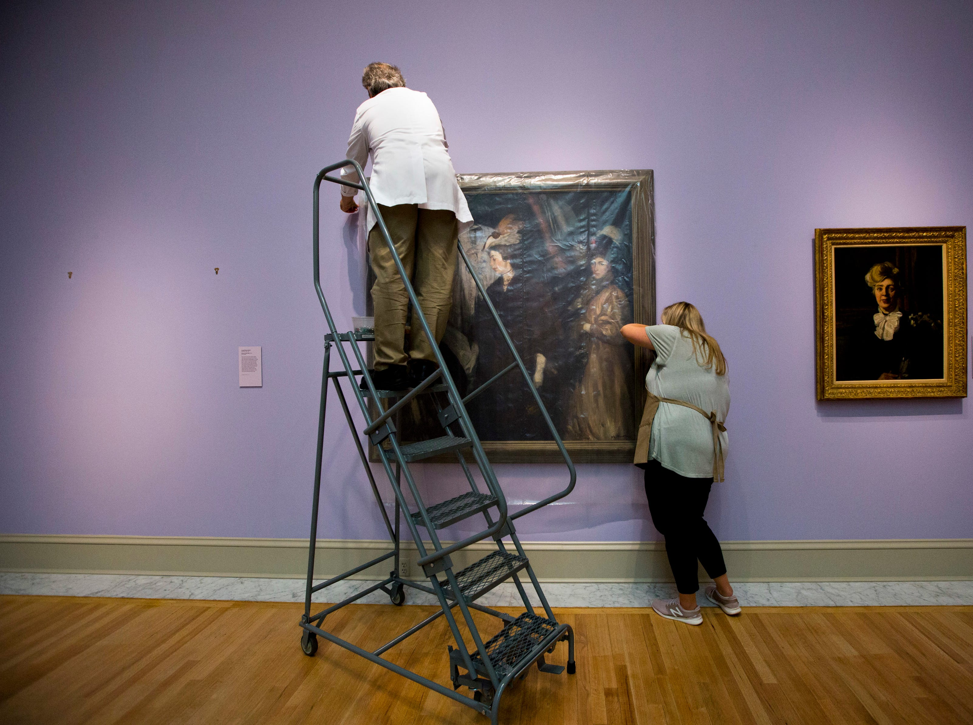 "Mark Lewis, left, conservator, and Alisa Reynolds, associate registrar, secure the painting ""The Shoppers"" by William James Glackens at the Chrysler Museum of Art on Tuesday, Sept. 11, 2018 in Norfolk, Va. As category 4 Hurricane Florence approaches, staff members pull priceless paintings off the walls near windows and skylights on. Later on, the entrance to the museum will be sandbagged."