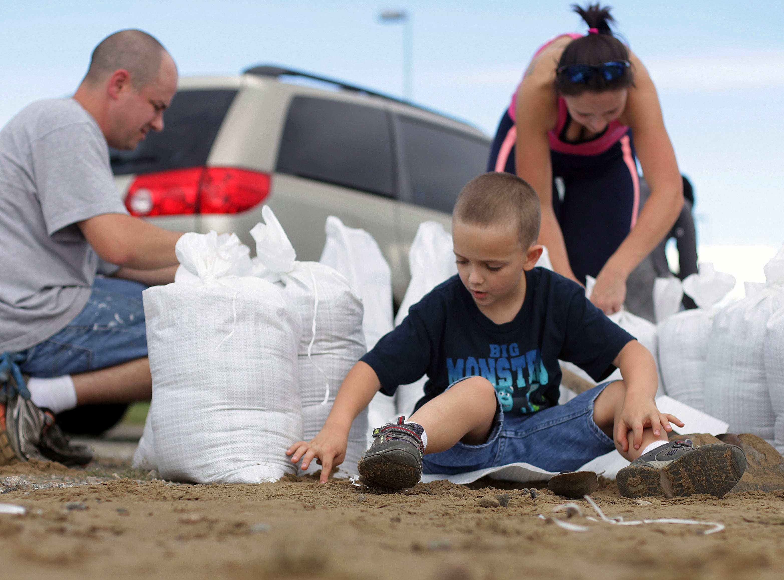 Topher Snyder, 7, plays in leftover sand as his parents Jeremy, left, and Tobi, center, tie off sandbags on Tuesday, Sept 11, 2018, in Virginia Beach. The city dumped mounds of free sand in one of the parking lots at the Virginia Beach Sportsplex for residents to use ahead of Hurricane Florence.