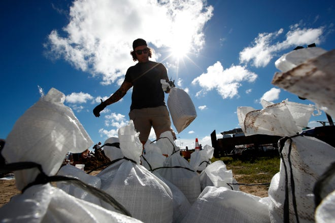 A Virginia Beach, Va., resident moves a sandbag before loading it in his truck, on Sept. 12, 2018, in Virginia Beach, Va., as Hurricane Florence moves toward the eastern shore.