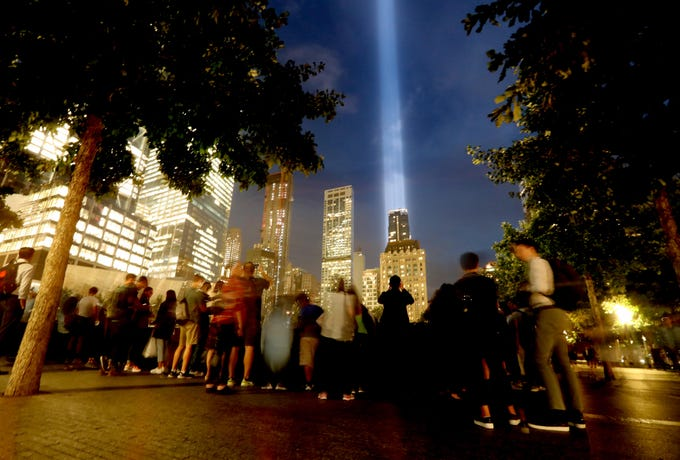 Visitors to the The National September 11 Memorial in New York watch the Tribute in Light on Sept. 11, 2018.