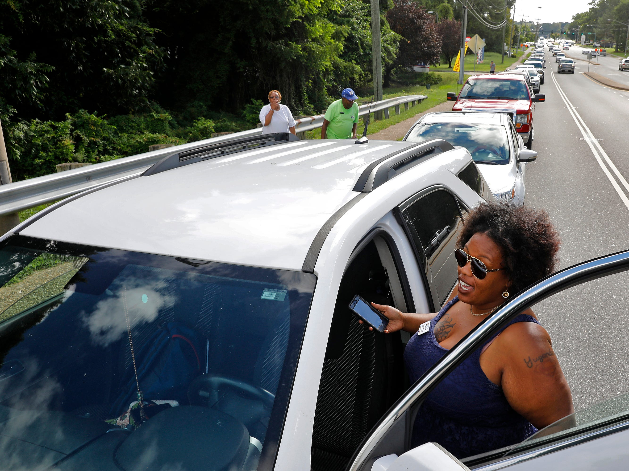 Yugonda Sample waits outside of her car as traffic backs up along Oyster Point Road as people attempt to pickup sandbags Wednesday, Sept. 12, 2018, in Newport News, Va. The city was offering free sandbags to residents at the Public Works Operations Center as Hurricane Florence approaches. Police had to turn away residents because of traffic congestion.