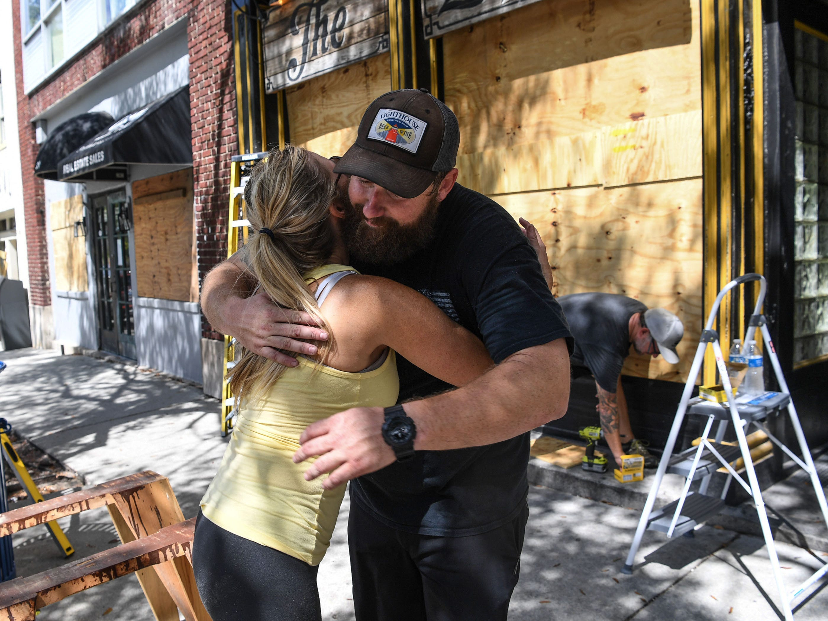Jennifer Wilson gives a hug to Andy Correll at The Liquid Room, a bar near the riverfront in Wilmington, N.C., Sept. 12, 2018, before the arrival of Hurricane Florence.