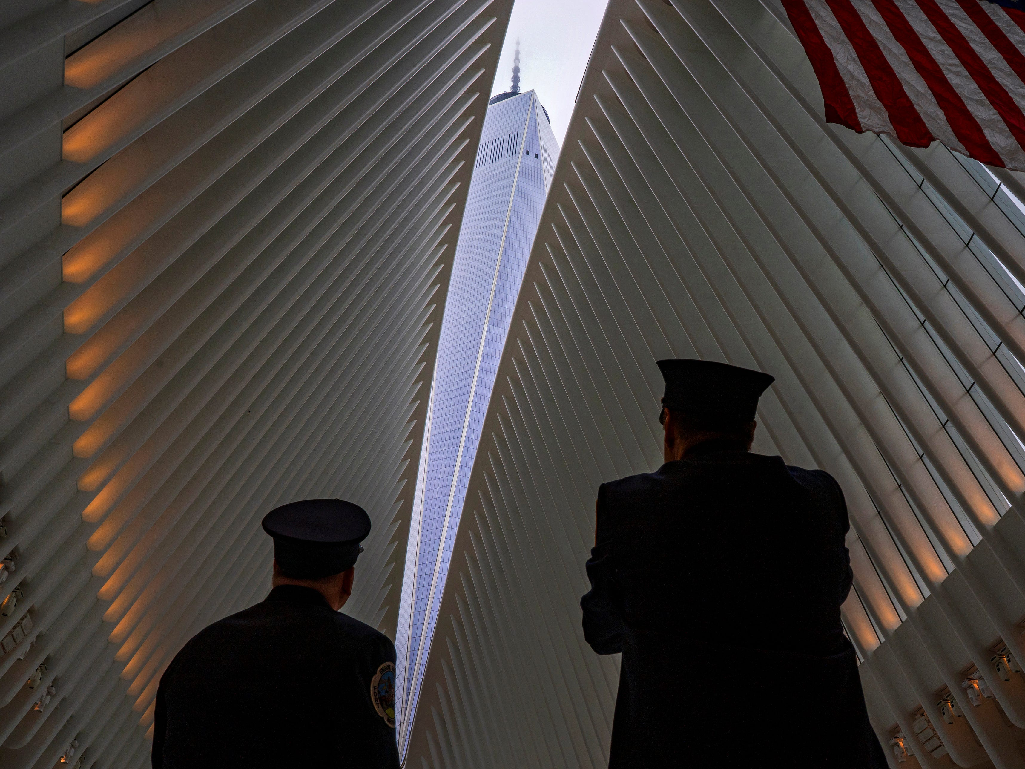 Two members of the New York City fire department look towards One World Trade Center through the open ceiling of the Oculus, part of the World Trade Center transportation hub in New York, on Sept. 11, 2018. The transit hall ceiling window was opened just before 10:28 a.m., marking the moment that the North Tower of the World Trade Center collapsed on September 11, 2001.