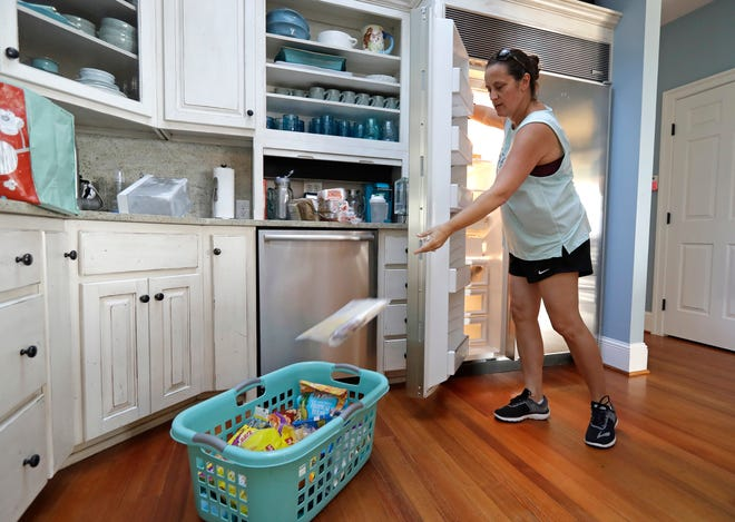 Michelle Stober, of Cary, N.C., removes food from a freezer as she prepares their vacation home in advance of Hurricane Florence in Wrightsville Beach, N.C., on Sept. 11. Florence exploded into a potentially catastrophic hurricane Monday as it closed in on North and South Carolina.